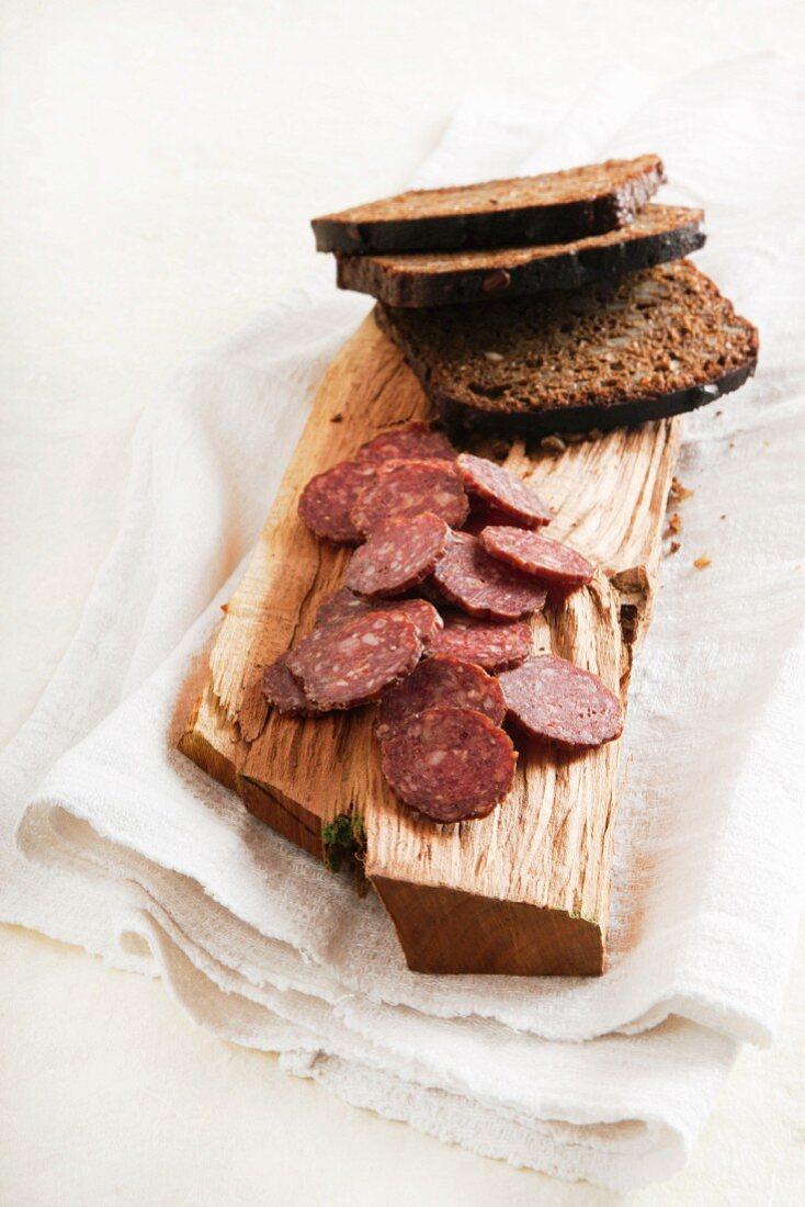 Elk salami and black bread on a wooden board (Estonia)