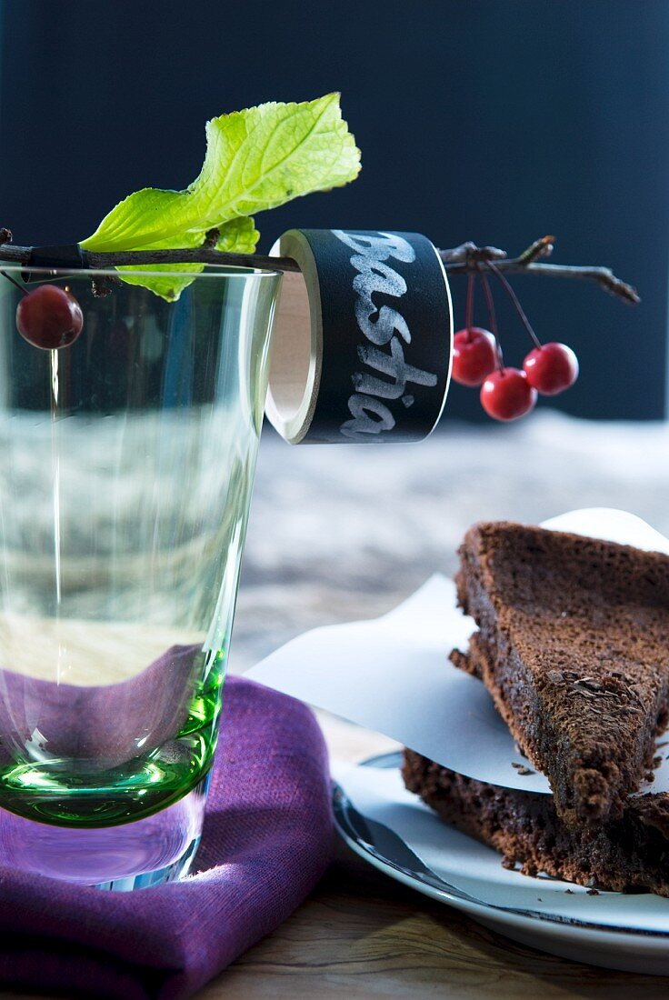 Two slices of chocolate cake and water glass with labelled napkin ring on cherry twig