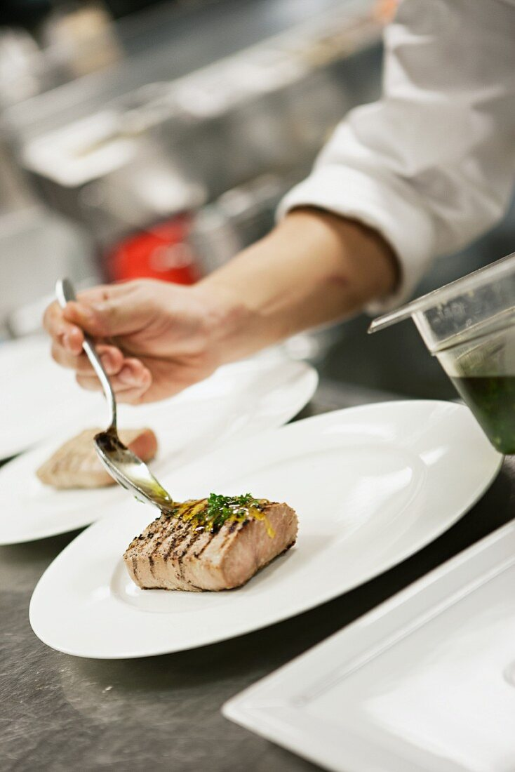A chef drizzling sauce on grilled tuna