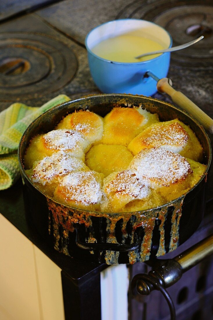 Dampfnudeln (steamed, sweet yeast dumpling) dusted with icing sugar in a pot