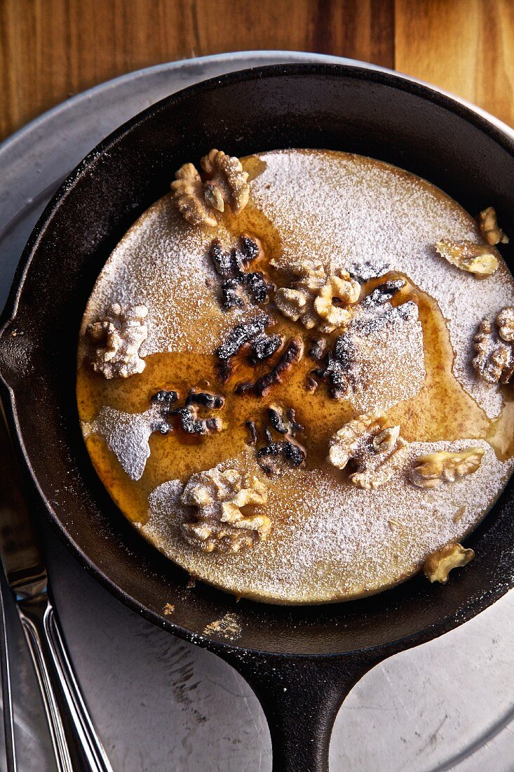 Pancake with walnuts and maple syrup in a pan (seen from above)