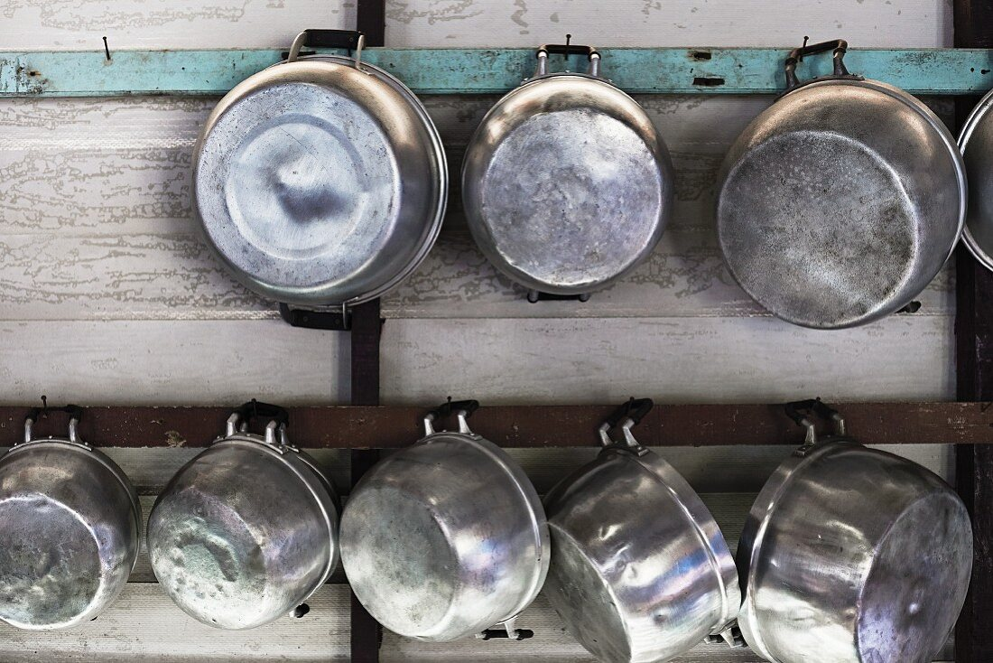 Metal pots hanging on a wooden wall