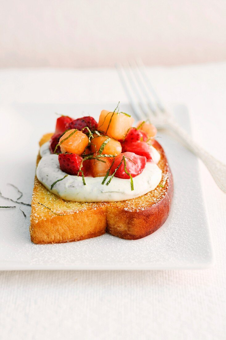 A slice of brioche topped with mint yogurt and strawberry and melon compote