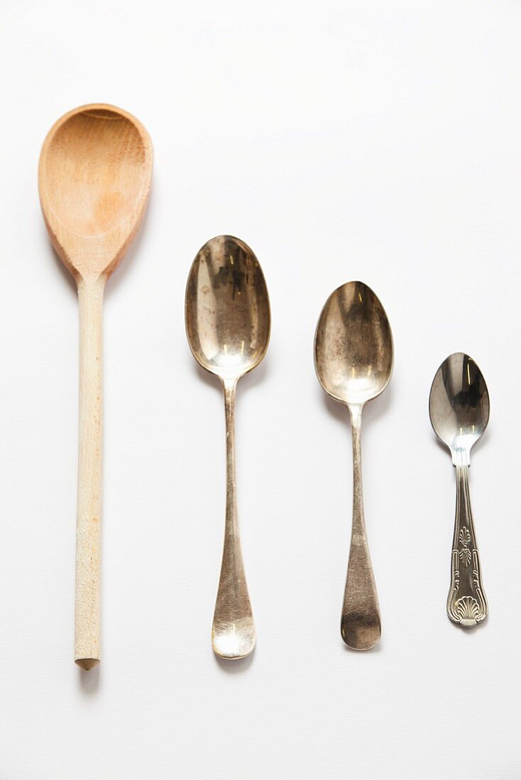 Wooden spoon and different sized metal spoons