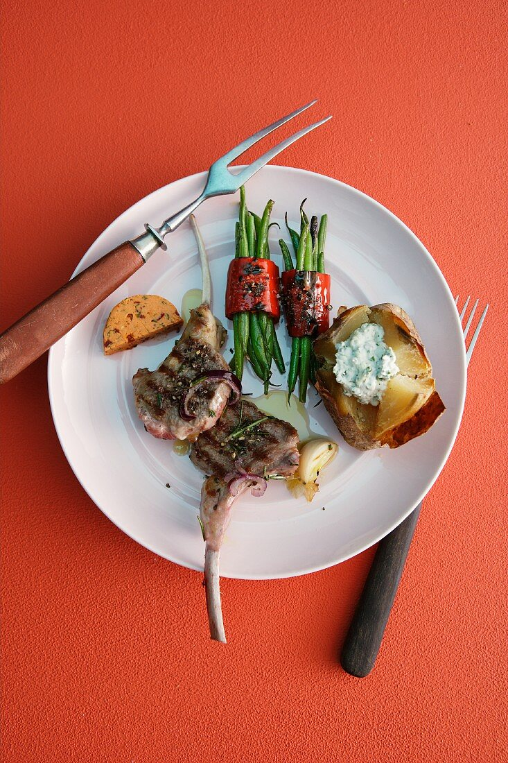 Lamb chops with bunches of beans, tomato butter and a baked potato
