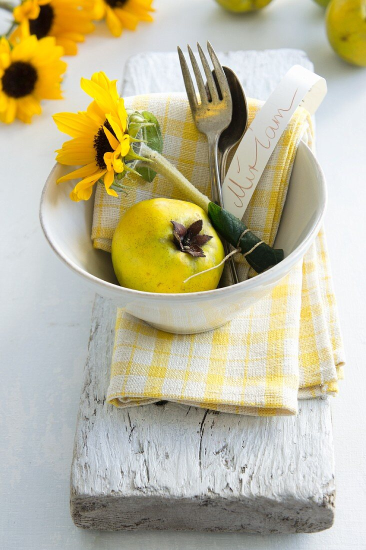 Cutlery, a sunflower and a quince in a bowl