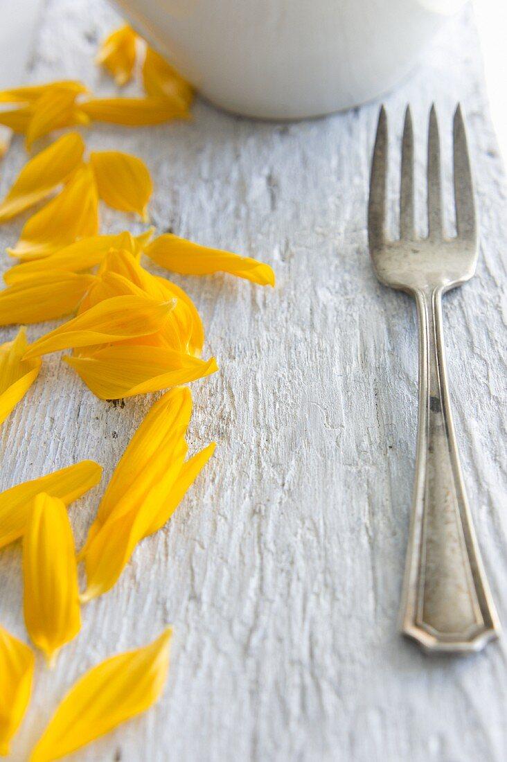 Sonnenblumenblütenblätter und Gabel auf Holzbrett