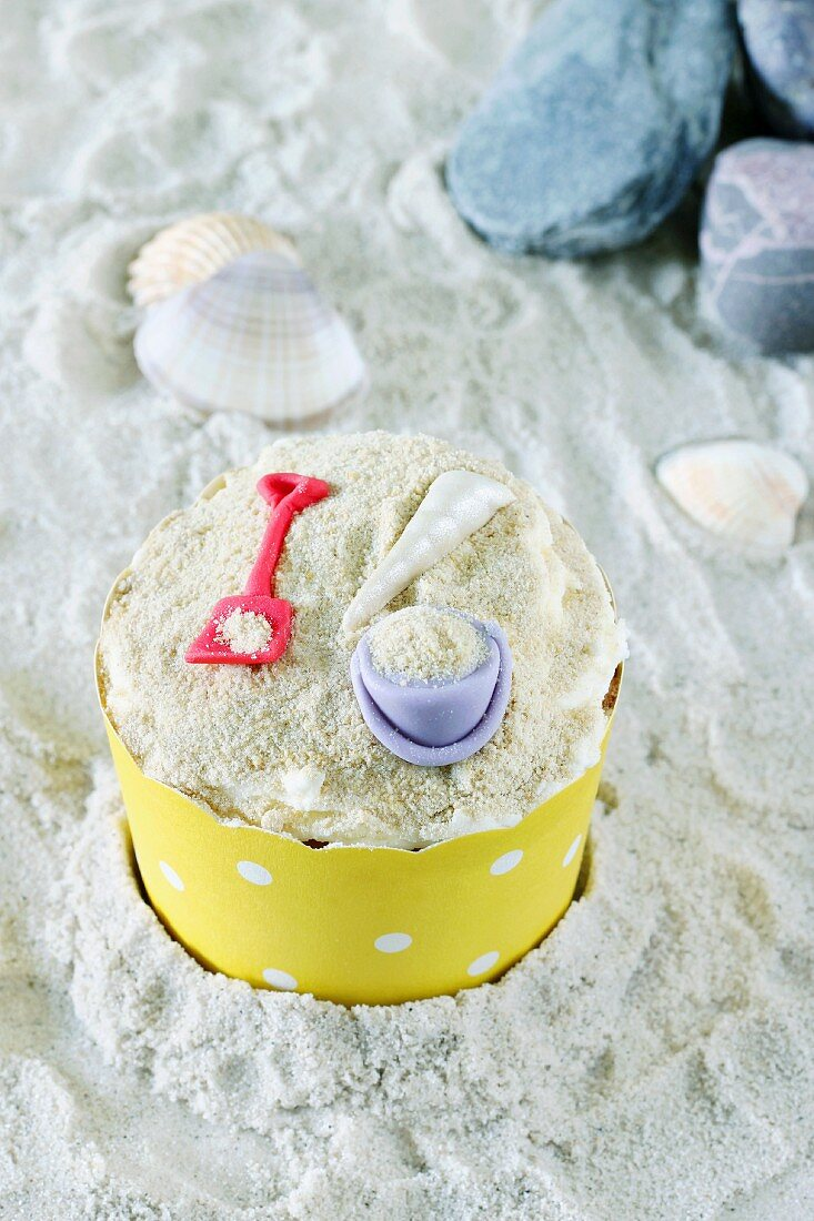A cupcake decorated with a bucket and spade