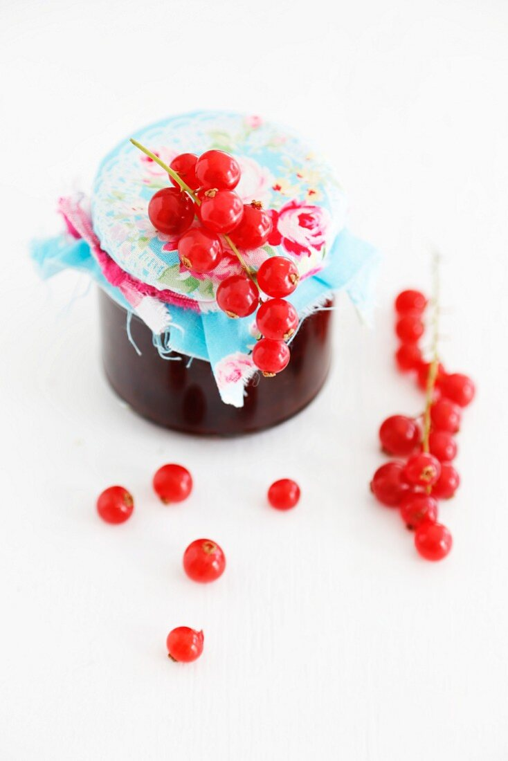 A jar on redcurrant jam with a fabric-covered lid