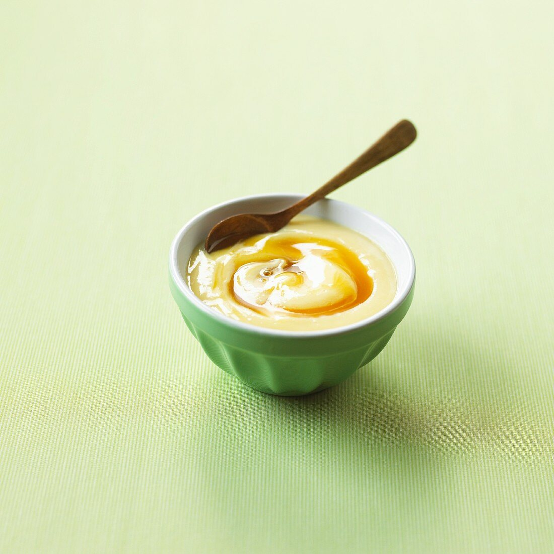 A bowl of custard with caramel sauce