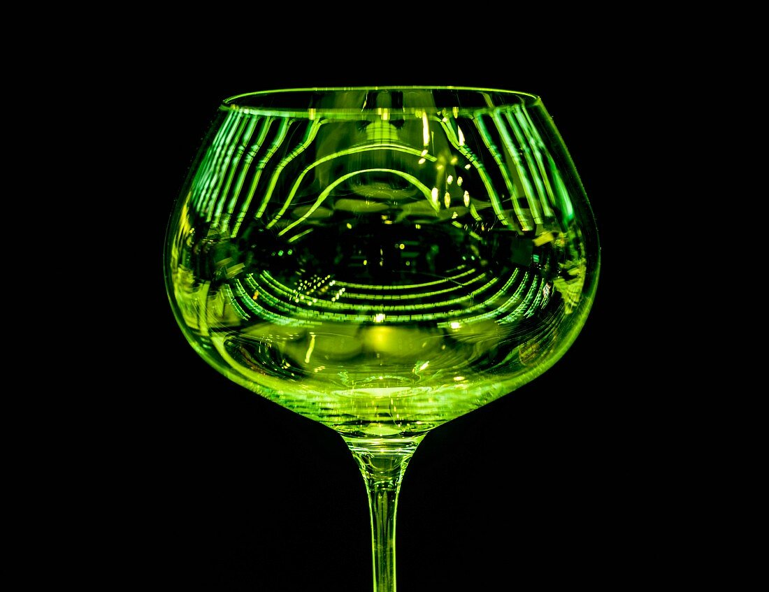 A green wine glass reflecting the light