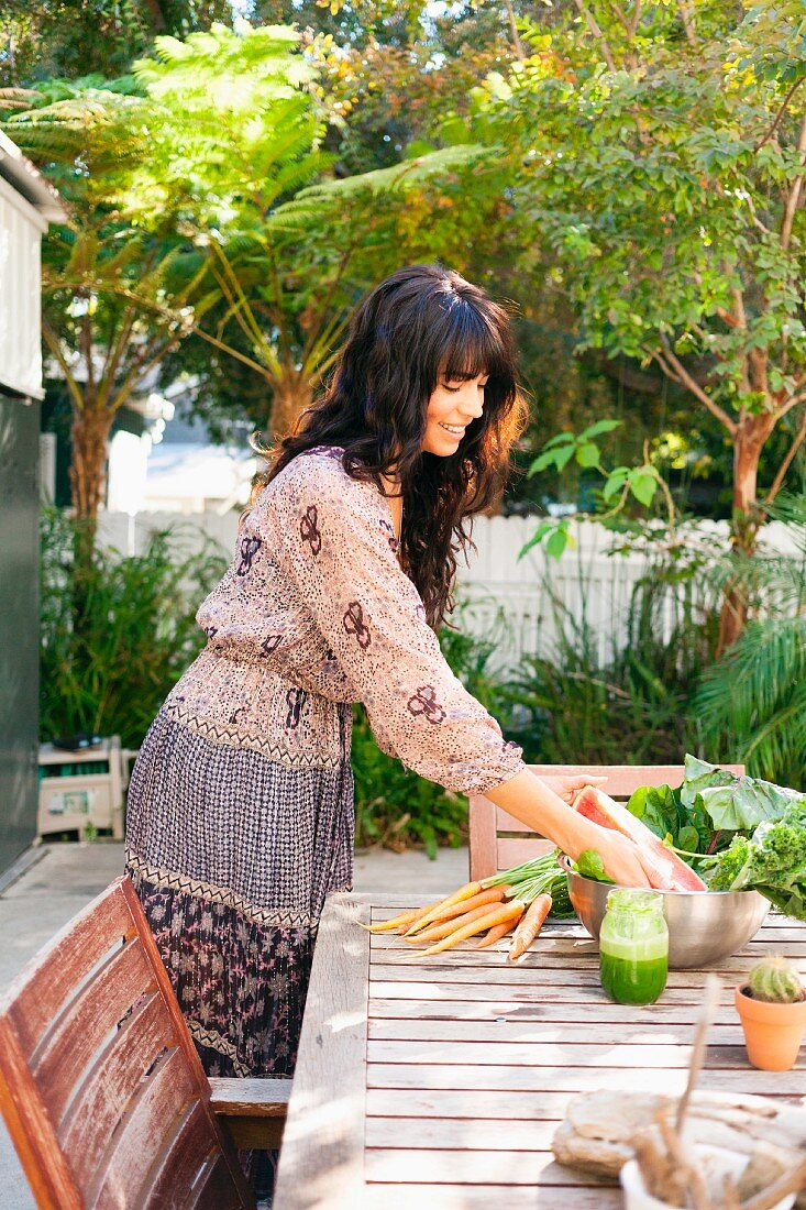 A young woman placing vegetables on a garden table