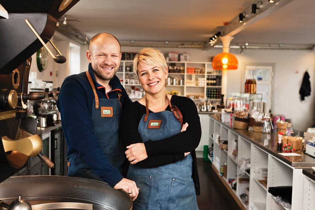 A smiling couple in the kitchen of their coffeeshop