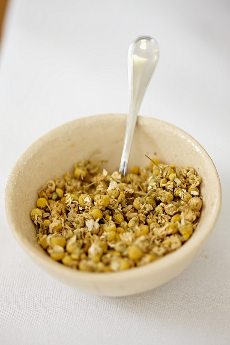 Dried camomile flowers in a bowl with a spoon
