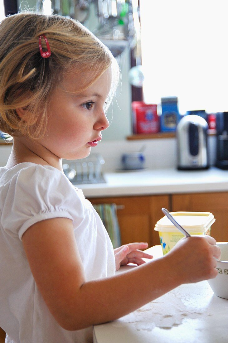 A little girl baking in a kitchen