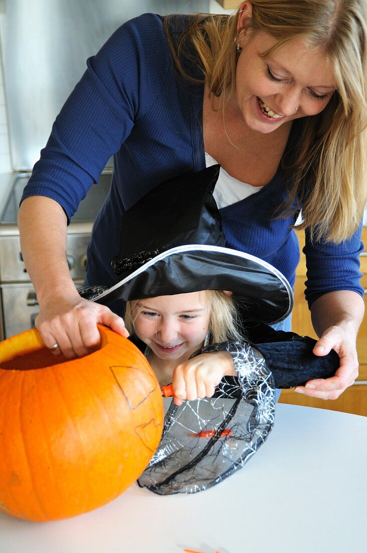 A mother and daughter preparing a Halloween pumpkin for carving