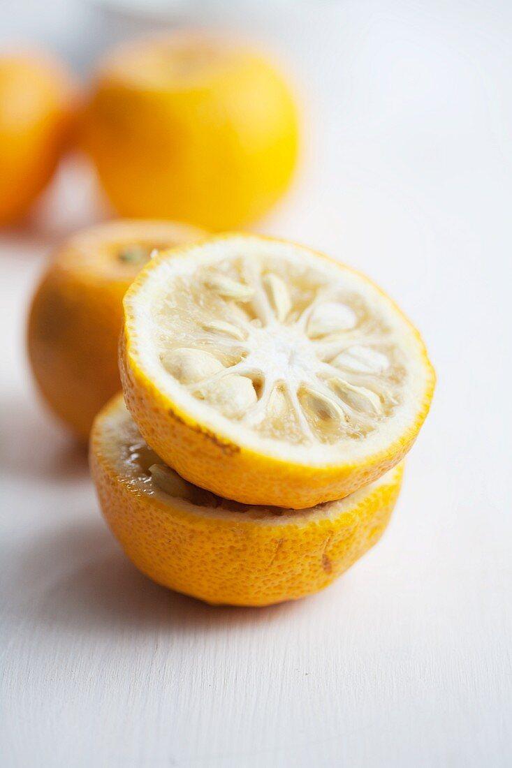 Yuzu in Hälften und ganze Früchte