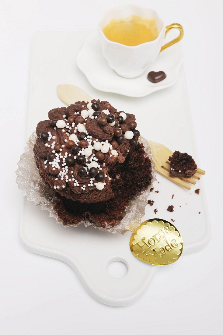 A chocolate cupcake decorated with sugar pearls with a bite taken out