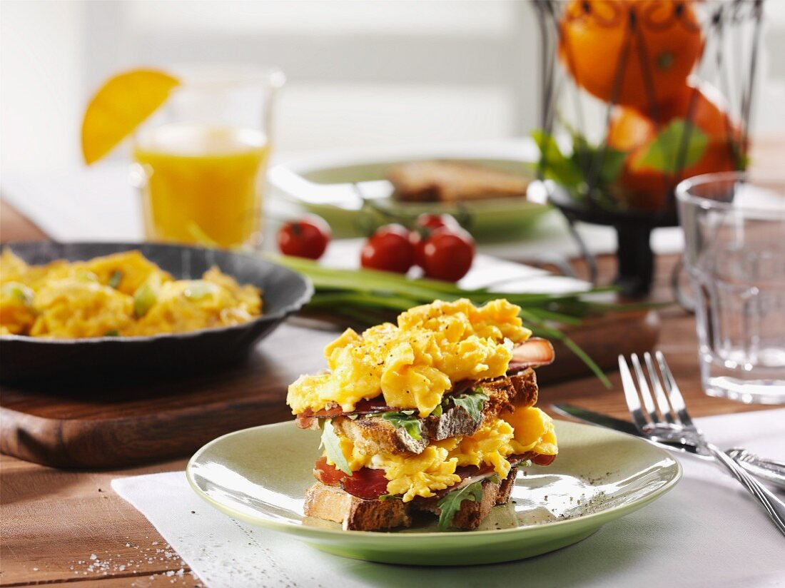 Taosted bread topped with scrambled eggs for breakfast