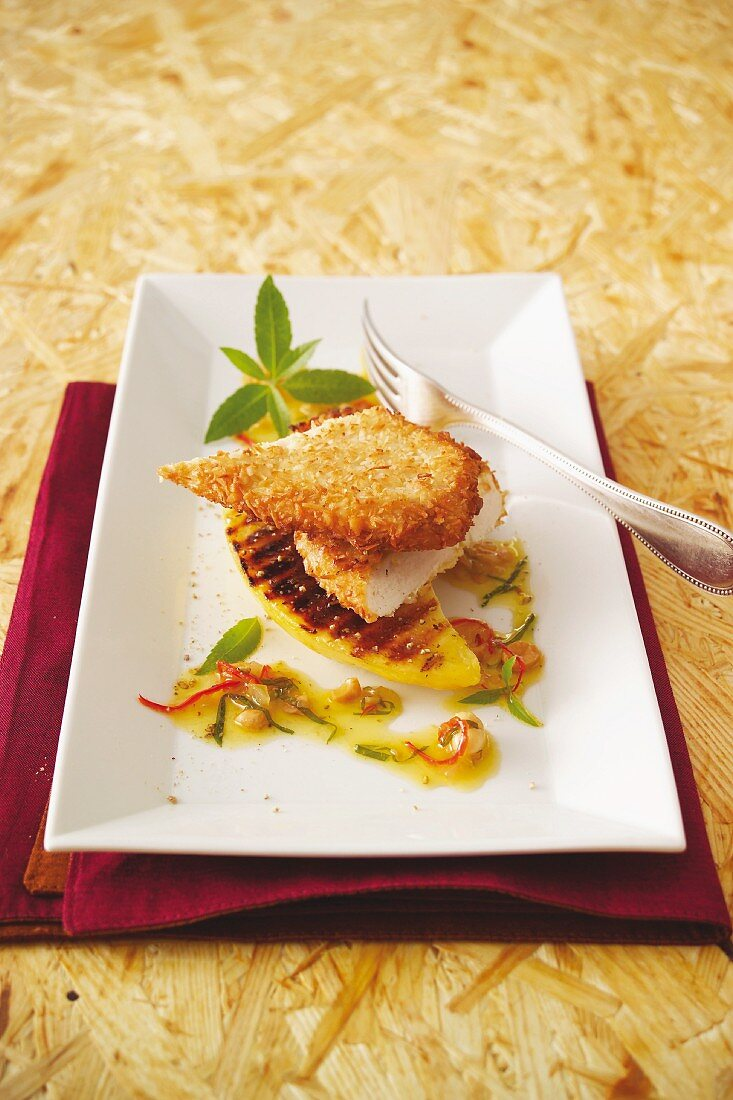 Guinea fowl escalope with a coconut coating served on grilled mango