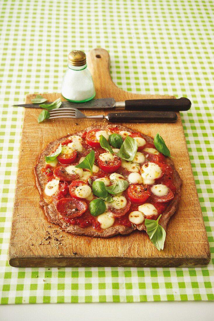 Schnitzelpizza mit Salami, Tomaten und Mozzarella
