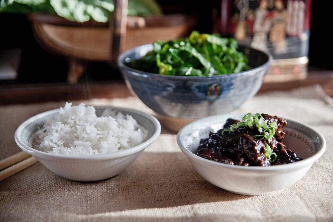 Slow-cooked beef in soy sauce seasoned with five-spice powder, sugar and chilli served with rice and green vegetables
