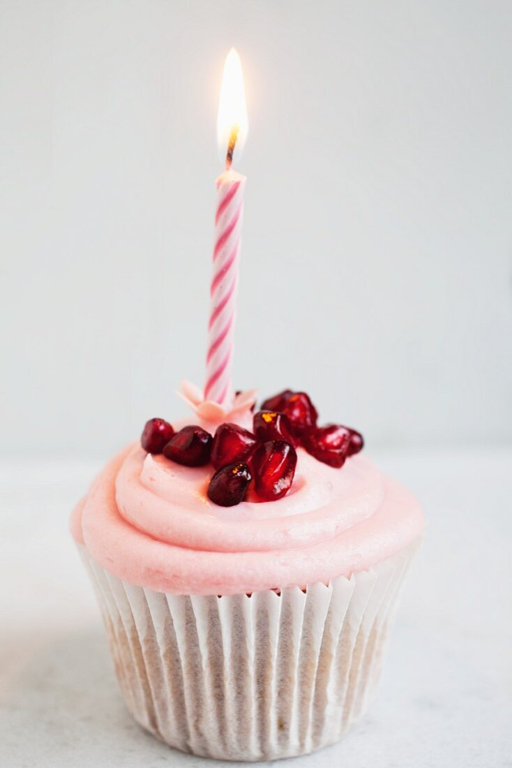 A birthday Cupcake with strawberry cream and pomegranate seeds