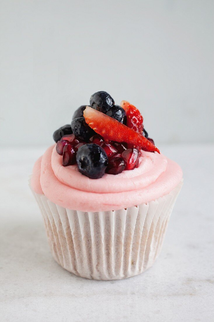 A strawberry and rhubarb cupcake with pomegranate seeds