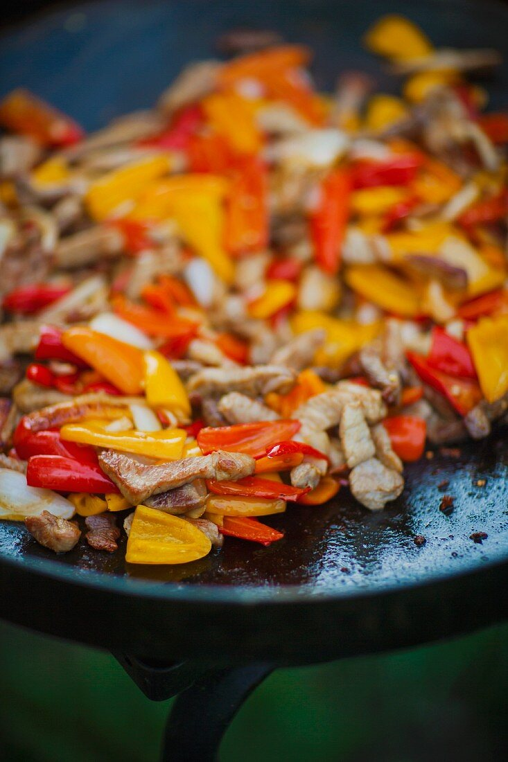 Fried pork with onions and peppers for fajitas