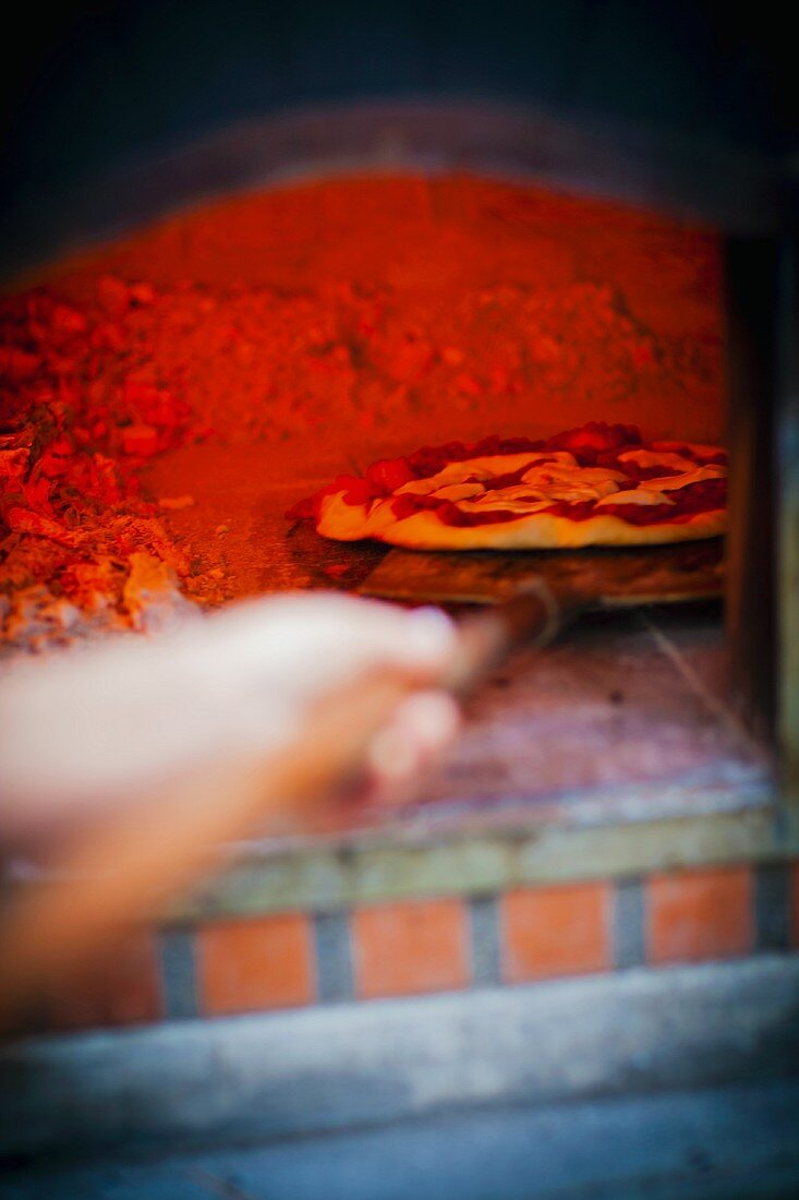 A pizza being pushed in to a hot, glowing wood-fired oven