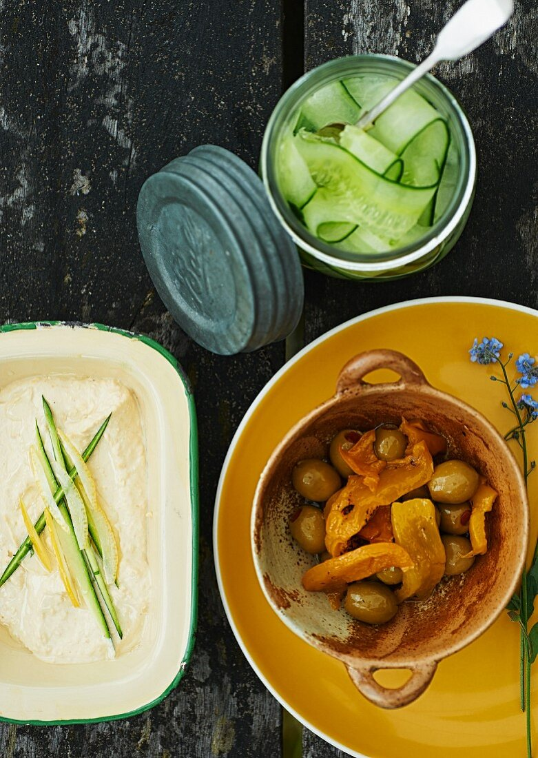 A picnic table with a pepper and olive medley, cucumber salad and vegetable cream