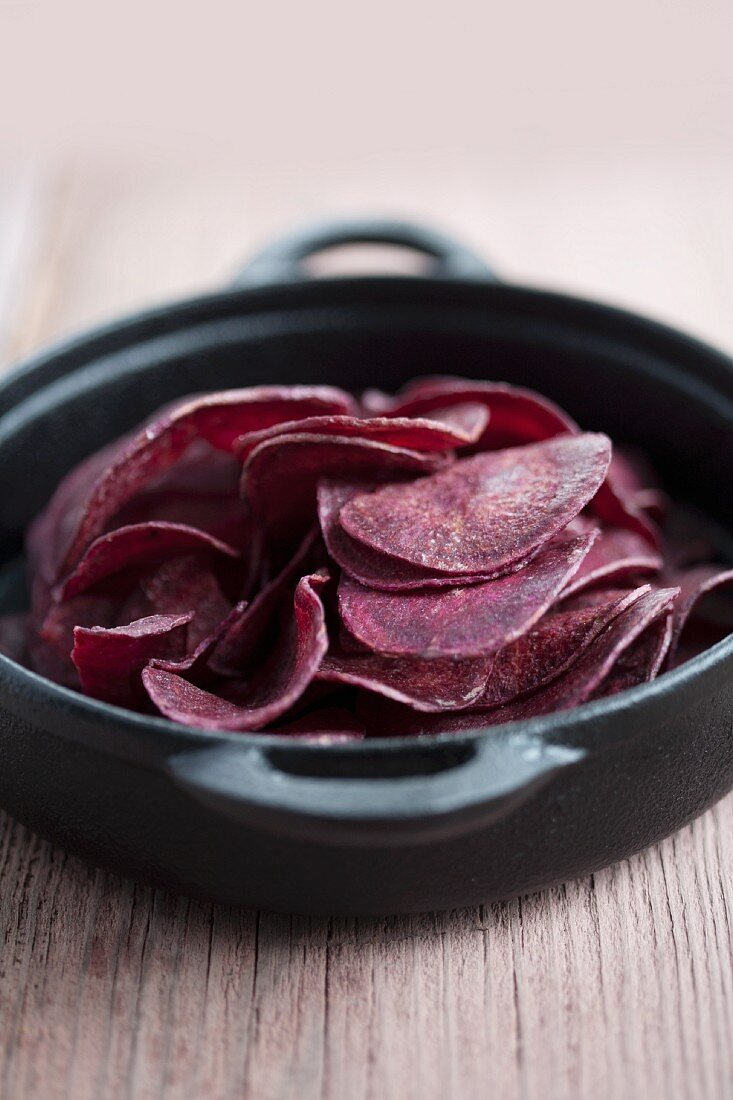 Purple potato crisps in a cast-iron pan