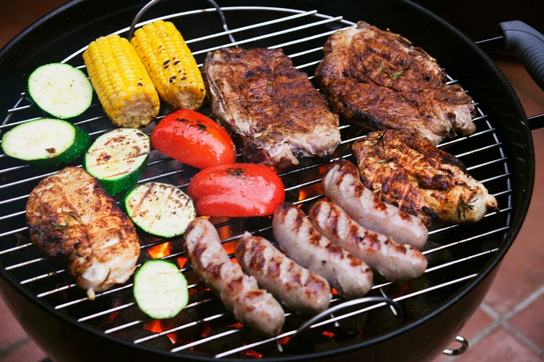Marinated pork steaks, sausages and vegetables on a barbecue