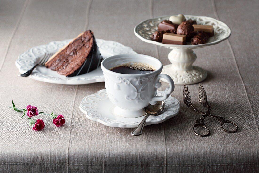 Kaffee in Tasse mit einem Tortenstück und verschiedenen Pralinen