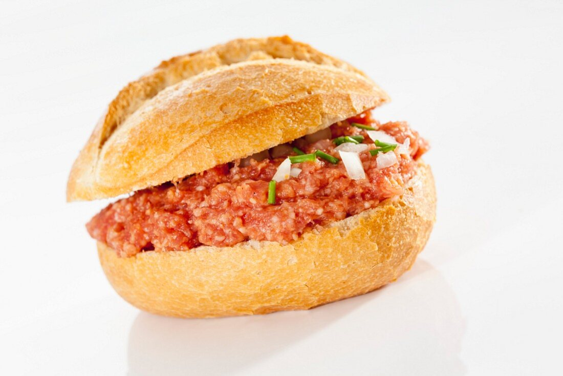 A crusty roll filled with raw minced meat and onions