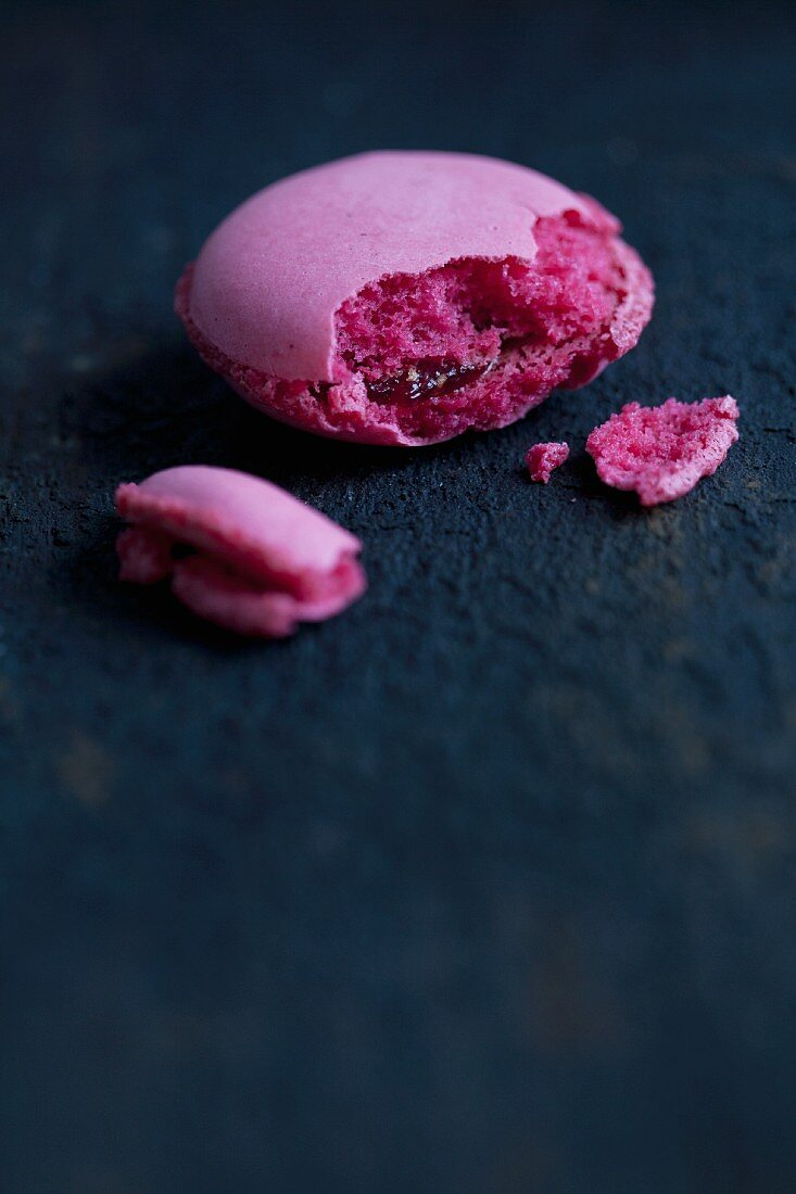 A cranberry macaroon with a bite taken out