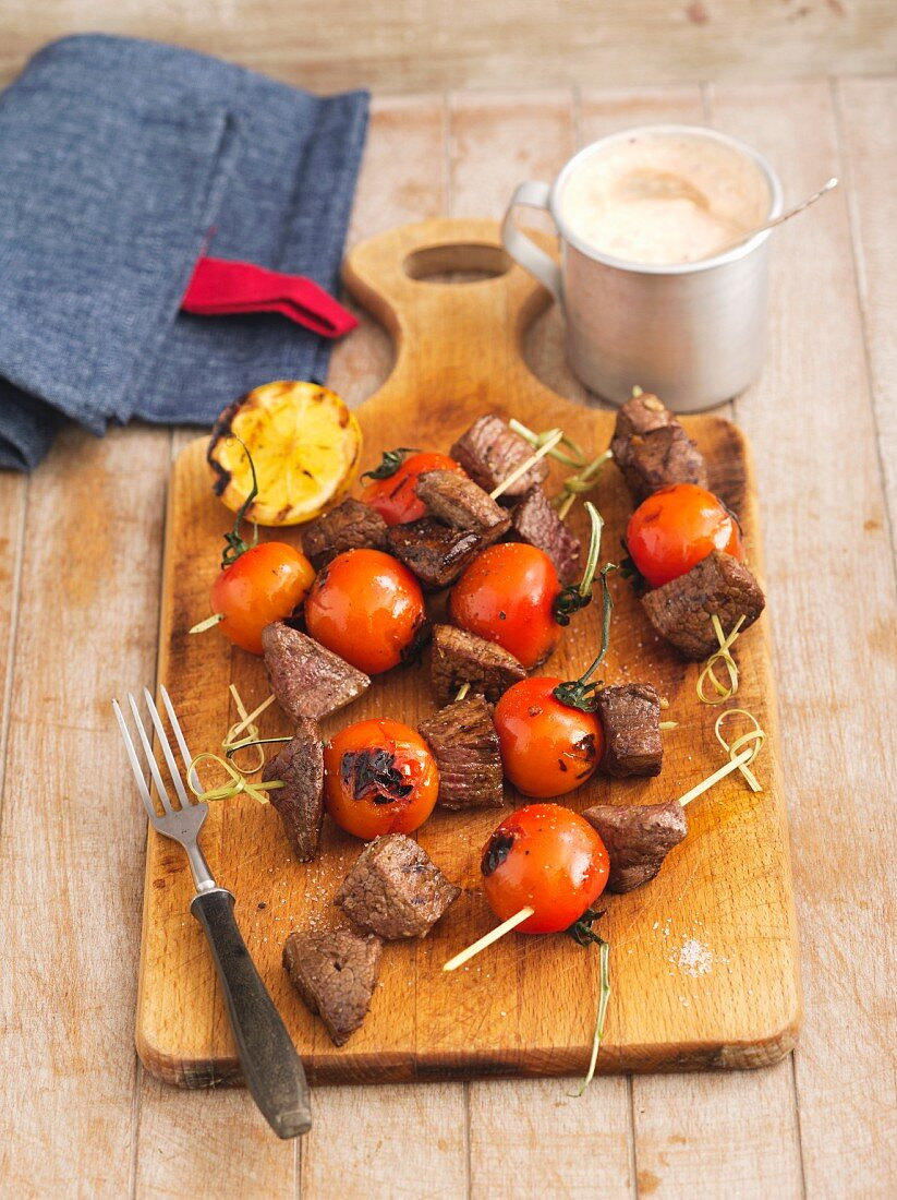 Grilled beef and tomato skewers on a wooden board