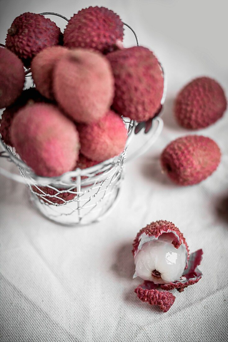 Lychees, some in a wire basket