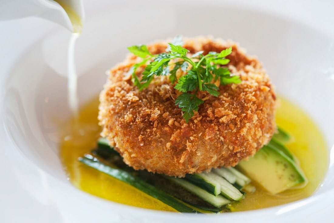 A crab cake with cucumber and avocado on lime consommé