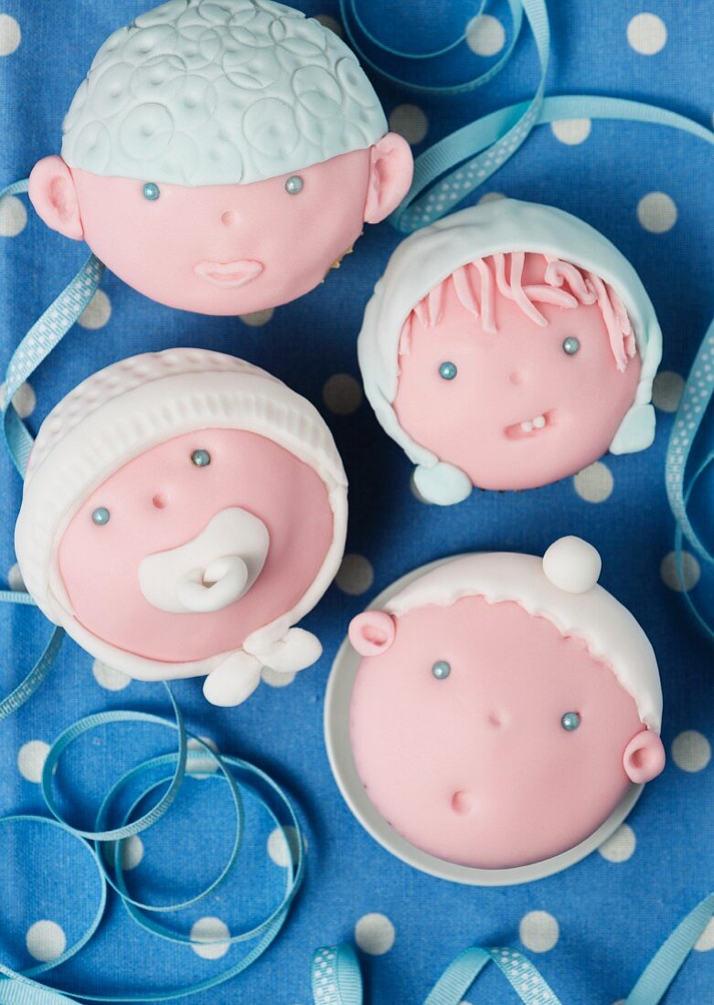 Cupcakes decorated with baby faces for a baby shower