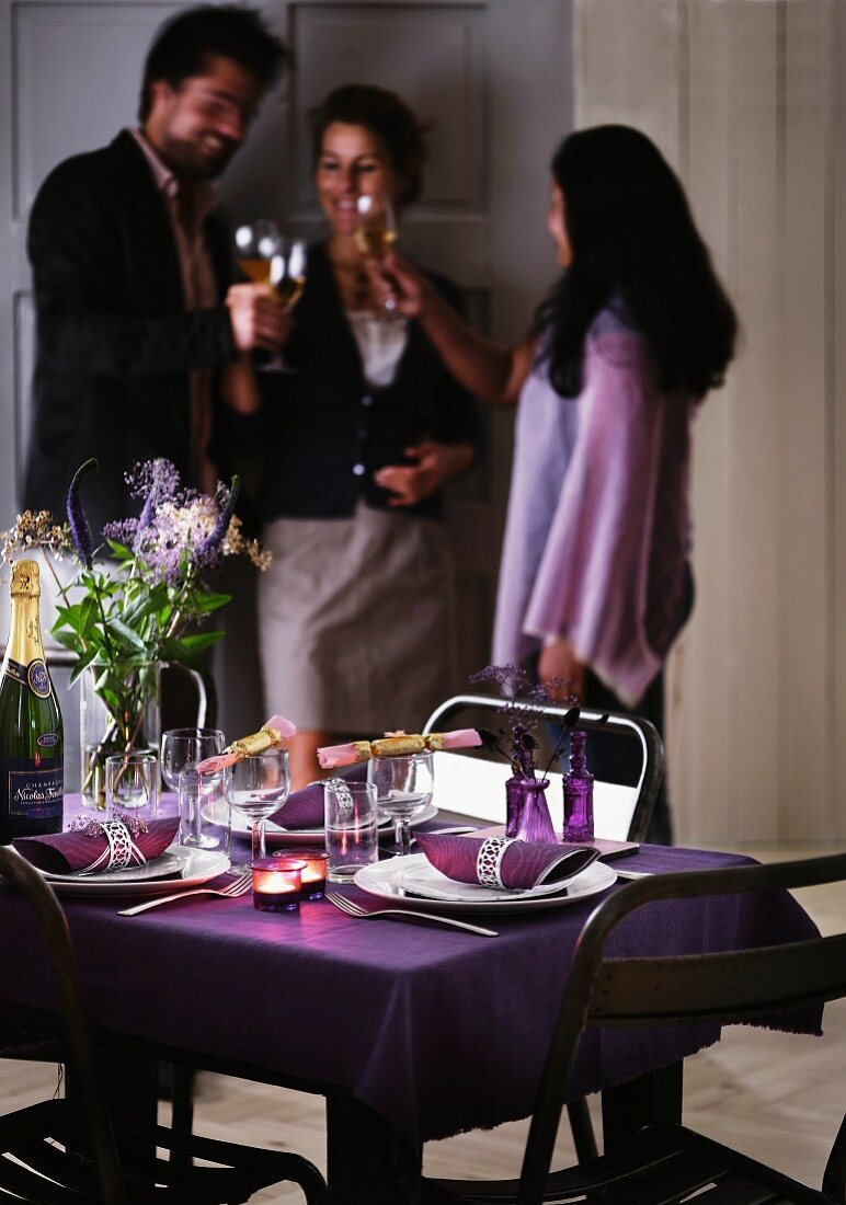 A table laid for Christmas with a purple tablecloth and napkins with silver rings; in the background three people with glasses of wine