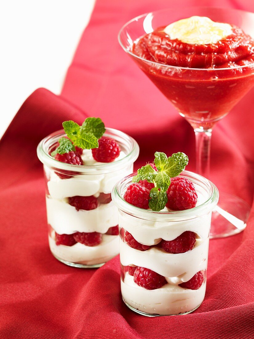 A raspberry and cream layered dessert and a strawberry and sour cherry smoothie