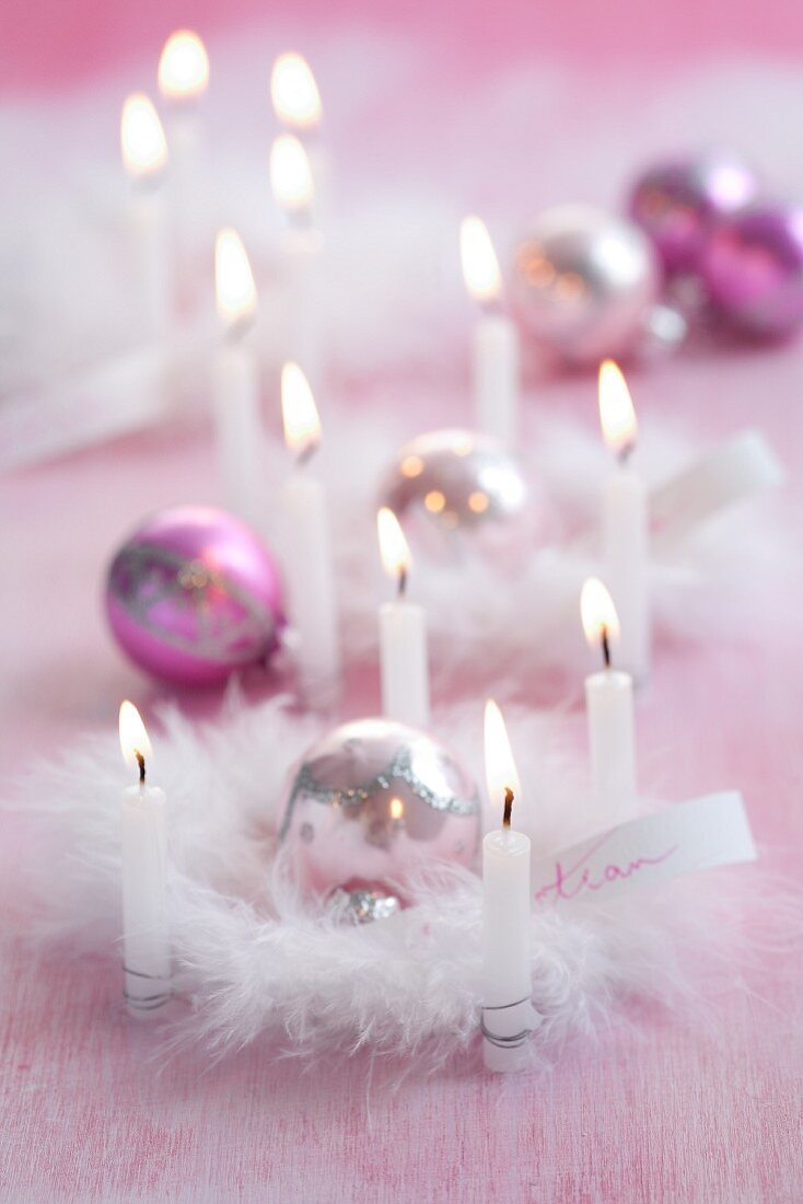 Pink Christmas arrangements of candles, baubles & feathers