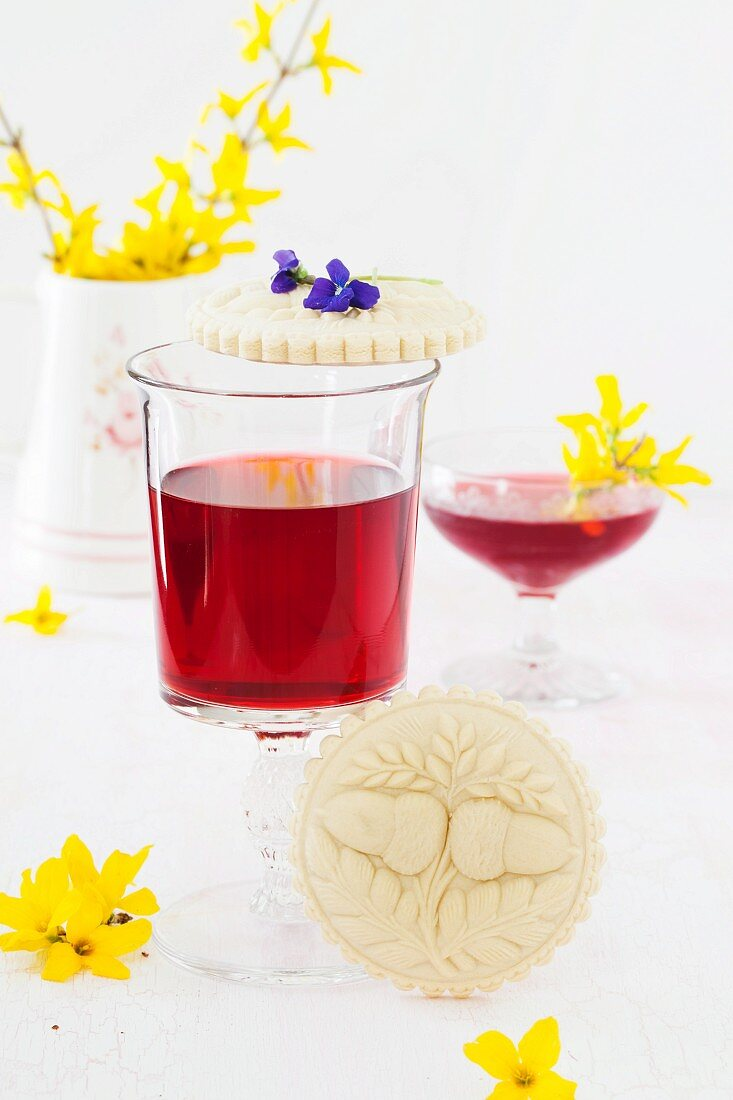 Springerle (anise biscuits with an embossed design) with spring flowers and strawberry wine