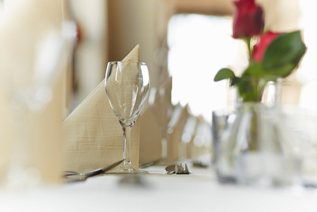 A glass on a laid table with a napkin in a restaurant