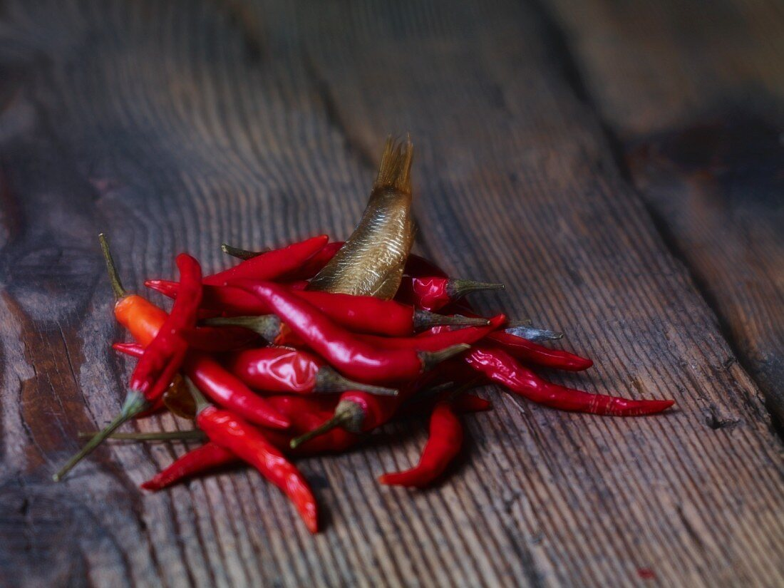 A sprat and fresh chilli peppers on a wooden surface