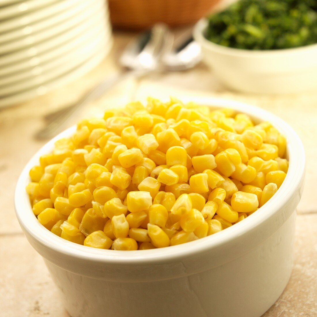 A bowl of sweetcorn with a bowl of spinach and a stack of plates in the background