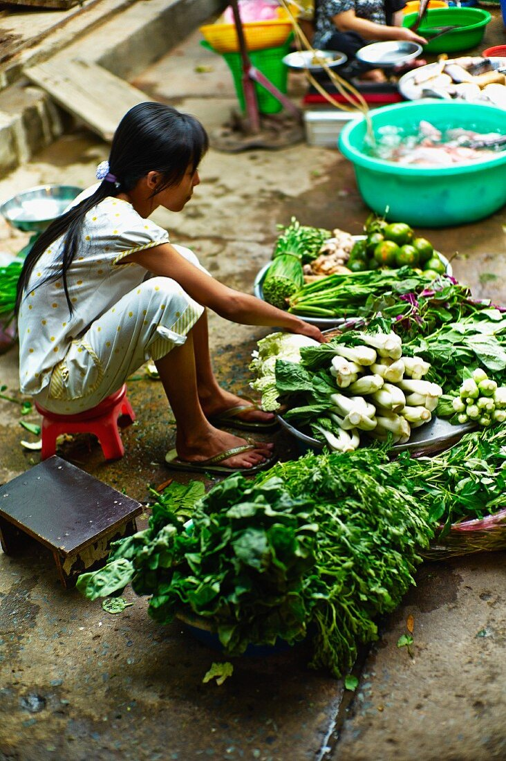 A girl selling vegetables at a market in Saigon (Vietnam)