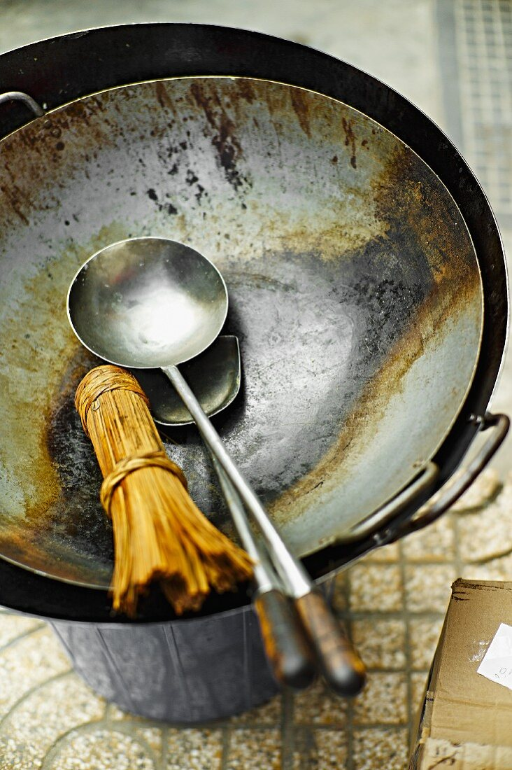 A bamboo whisk, a ladle and a spatula in a wok at a market in Saigon (Vietnam)