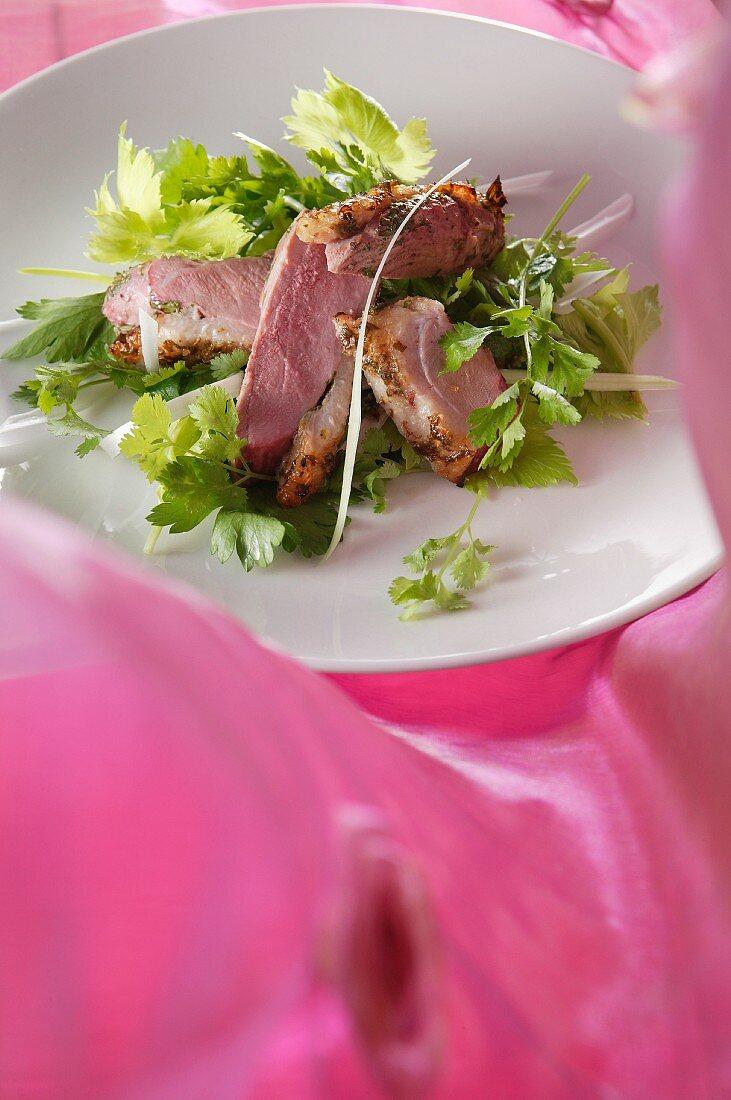 Medium rare duck breast on a bed of celery salad